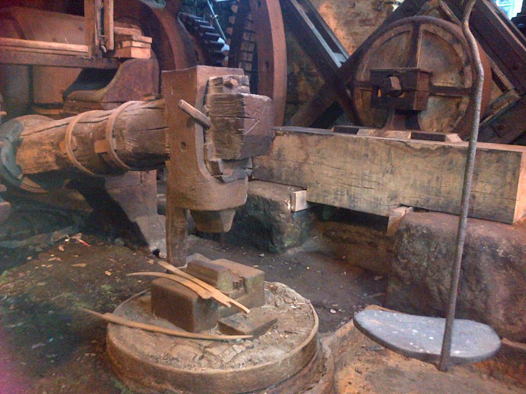A tilt hammer. The worker sat on the metal