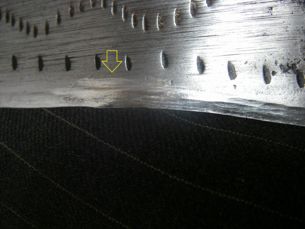 A nicely peened blade edge. Arrow points to repaired damage.
